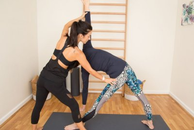 An instructor helps a women into the correct yoga pose