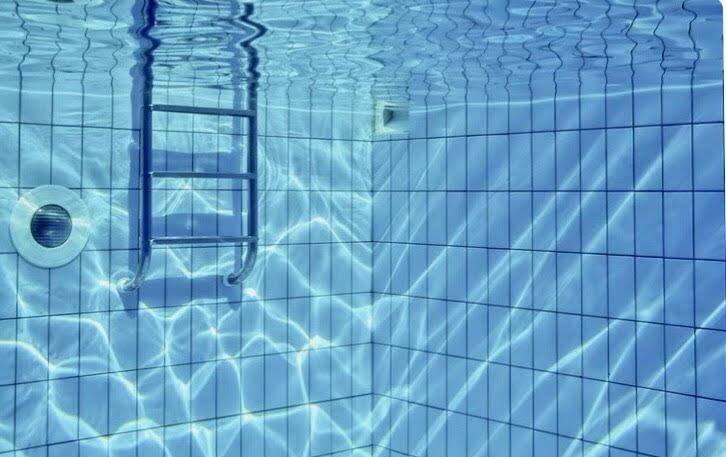 underwater shot inside a hydrotherapy pool with a ladder to the left